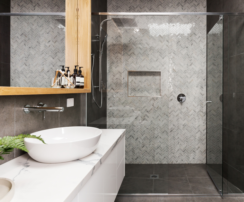 A glass shower enclosure that features black and white tiled walls